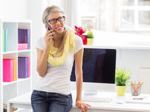 Creative woman talking on phone in the office Royalty Free Stock Images