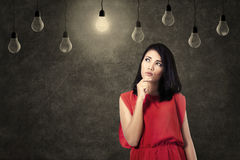 Creative woman thinking of ideas. Creative woman looking at bright lightbulb royalty free stock photography