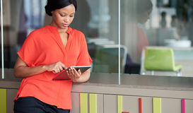 Creative woman using digital tablet while leaning against colourful cabinet Stock Photography