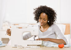 Creative woman using sewing machine. To sew clothing stock image