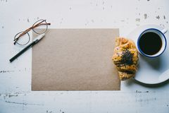 .Creative work concept.Mock-up blank craft sheet of empty paper, pen, eye glasses and morning coffee cup with croissant. On white wooden desk. Business Royalty Free Stock Photos