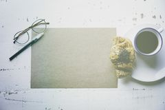 .Creative work concept.Mock-up blank craft sheet of empty paper, pen, eye glasses and morning coffee cup with croissant. On white wooden desk. Business Royalty Free Stock Image