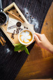 Creative work with a cup of boiling water in his hands. A handfu. L of coffee, green, ground and soluble coffee leaves on a wooden table top white, black and Royalty Free Stock Photos