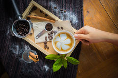 Creative work with a cup of boiling water in his hands. A handfu. L of coffee, green, ground and soluble coffee leaves on a wooden table top white, black and Stock Images