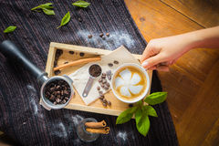 Creative work with a cup of boiling water in his hands. A handfu. L of coffee, green, ground and soluble coffee leaves on a wooden table top white, black and Stock Image