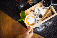 Creative work with a cup of boiling water in his hands. A handfu. L of coffee, green, ground and soluble coffee leaves on a wooden table top white, black and Royalty Free Stock Image