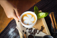 Creative work with a cup of boiling water in his hands. A handfu. L of coffee, green, ground and soluble coffee leaves on a wooden table top white, black and Royalty Free Stock Photography