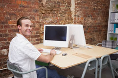 Creative worker typing on laptop at his desk Royalty Free Stock Photography