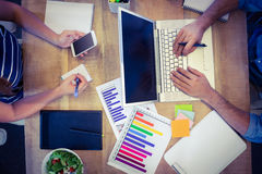 Creative workers sharing desk Royalty Free Stock Photos