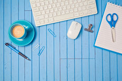 Creative workplace concept with keyboard, coffee cup and notebook on wooden blue table. Royalty Free Stock Photo