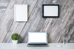Creative workplace with picture frames. Creative designer workplace with blank white laptop computer, plant, mouse, water glass and two picture frames hanging Stock Photography
