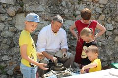 Creative workshop of traditional handcrafts - potter teaches children how to make pottery on potter´s wheel. Creative workshop of traditional handcrafts stock photography