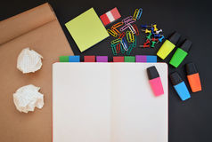 Creative workspace with open notebook, craft, colorful highlighters, clips and pins on black desk Stock Images