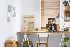 Creative workspace with scandinavian, wooden furniture, white walls and sewing tools in a modern crafts room interior. Real photo. Concept stock images