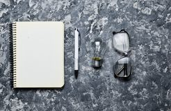 The creative workspace of the writer is inspiring to create. I have an idea. Notepad, pen, incandescent bulb, glasses. On a concrete table. Top view. Flat lay Royalty Free Stock Photos