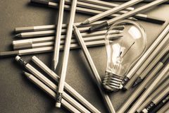 Creative writing. Light bulb and many pencils on the table Royalty Free Stock Photos