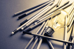 Creative writing. Light bulb and many pencils on the table Royalty Free Stock Images