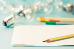 Creative writing. Pen on clear paper with light bulb as creative writing concept Royalty Free Stock Photo