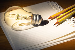 Creative writing. Pencils and light bulb on papers, creative writing concept Stock Images