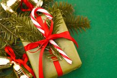 Gift box in green wrapping paper, candy, xmas bells, pine on red background. Copy space. Closeup Royalty Free Stock Photos