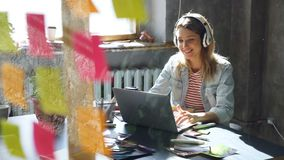 Creative young businesswoman is listening to music in headphones dancing while working at desk with laptop in modern