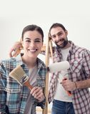 Creative couple renovating their house. Creative young couple renovating their house and painting walls, they are posing together and smiling at camera Stock Photo