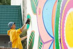 Creative young man drawing with spray can on wall Royalty Free Stock Photos