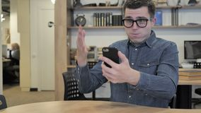Creative Young Man in Glasses Reacting to Loss while Using Smartphone stock video footage