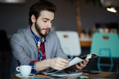 Creative Young Man Reading Magazine in Cafe Royalty Free Stock Photo