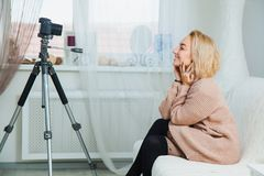 Creative young woman recording video blog for social media network. Blogging concept. Young female vlogger next to video camera at home, vlog message for stock photography