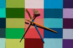 Creatively placed paint brushes on bright tiles. Creatively placed paintbrushes painted summer spring colors on wooden tiles Stock Photos