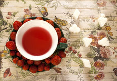 Creatively served fruit tea and strawberries on saucer Royalty Free Stock Images