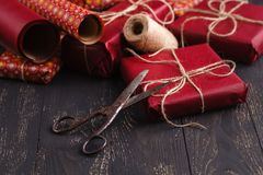 Creatively wrapped and decorated christmas presents in boxes on wooden background. Copy space. Stock Photos