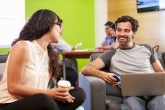 Creatives Having Informal Meeting On Sofas In Design Studio Royalty Free Stock Images