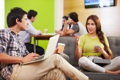 Creatives Having Informal Meeting On Sofas In Design Studio Stock Photo