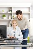 Creatives novos que trabalham junto com o computador Fotografia de Stock Royalty Free
