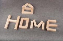 creativiteit Word het huis en het kleine die stuk speelgoed cijfer van houten blokken wordt gemaakt leggen op grijze achtergrond Royalty-vrije Stock Foto