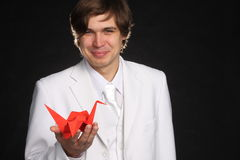 Creativity. Conceptual picture about creativity, beautiful smiling man with red paper crane in hand Royalty Free Stock Image