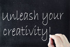 Creativity. Unleash your creativity handwritten on a blackboard stock photos