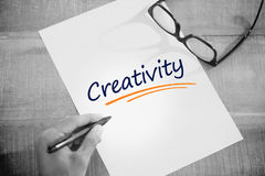 Creativity  against left hand writing on white page on working desk Stock Image