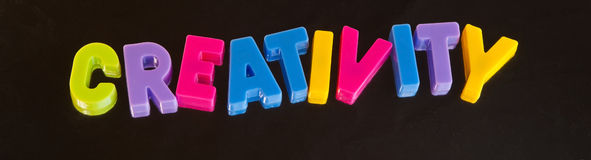 Creativity. Banner or logo reading ' creativity ' in colorful uppercase letters on a dark background providing logo or banner Stock Image