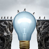 Creativity Business. Idea solution as a group of people on two divided cliffs being connected by a giant light bulb closing the gap and creating a bridge to Stock Photography