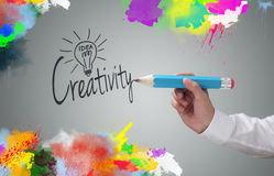 Creativity. Businessman writing the word creativity and painting abstract colorful design on gray background concept for business idea, imagination and royalty free stock photos
