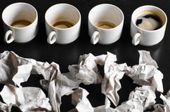 Creativity concept. Business creativity concept. empty and full cups of fresh espresso with crumple wads on desk Stock Photography