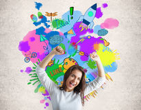 Creativity concept. Cheerful caucasian woman on concrete background with colorful sketch. Creativity concept stock photo