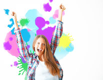 Creativity concept. Cheerful eurpean girl on light background with colorful splashes. Creativity concept royalty free stock image