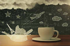 Creativity concept. Close up of coffee cup with abstract stravel sketch, airplane, mathematical formulas in the background and clouds. Creativity concept 3D Royalty Free Stock Photography