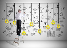 Creativity concept drawn by a man on a ladder. Man on a ladder drawing creativity concept on a wall Stock Photo