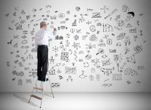 Creativity concept drawn by a man on a ladder. Man on a ladder drawing creativity concept on a wall royalty free stock images