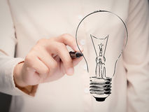 Creativity concept with hand drawing lightbulb. Creativity concept with woman`s hand drawing lightbulb royalty free stock photos